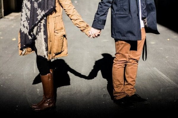 a couple facing away from each other yet holding hands