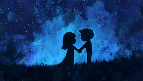 a boy and girl holding hands in a field at night