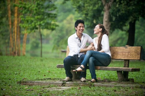 A couple is laughing on a park bench.