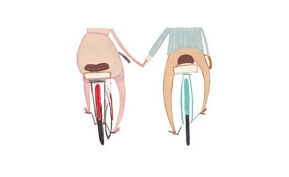 a couple riding bikes, holding hands