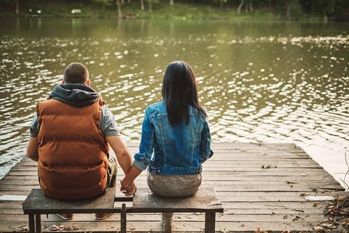 A couple is sitting in front of a lake holding hands.