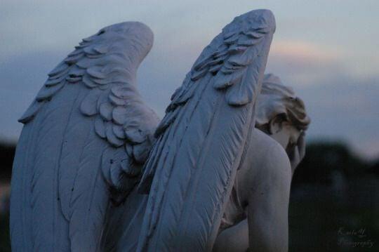 an angel statue looking depressed