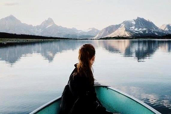 a woman in a rowboat on a mountain lake thinking about what makes you happy