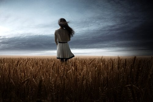a girl in a field of wheat, pondering opportunities