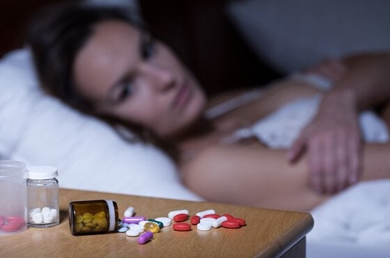 a woman looking at insomnia medication on the night stand