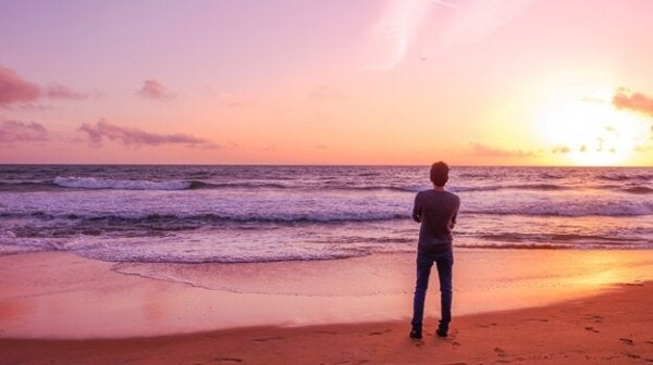 a lone man looking at the ocean with his arms crossed