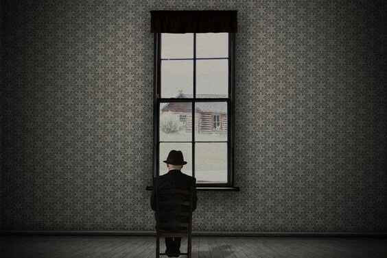 A man is looking out the window to a winter landscape.
