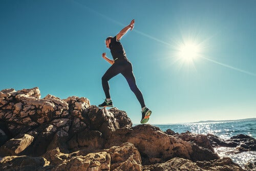 a runner leaping up a hill by the water
