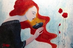 A redheaded woman is smelling a flower.