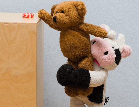 A stuffed cow is helping a stuffed bear reach something.