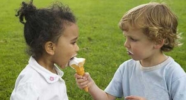 Two kids are sharing an ice cream cone and one is being a good person