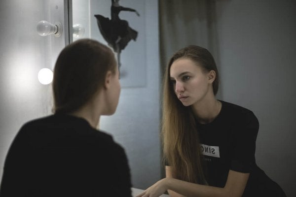 a woman looking into the mirror, sad