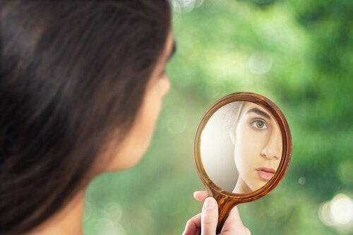 A woman looking at herself in a hand mirror.