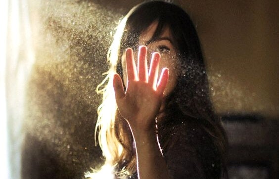 a woman putting her hand in a ray of sunlight