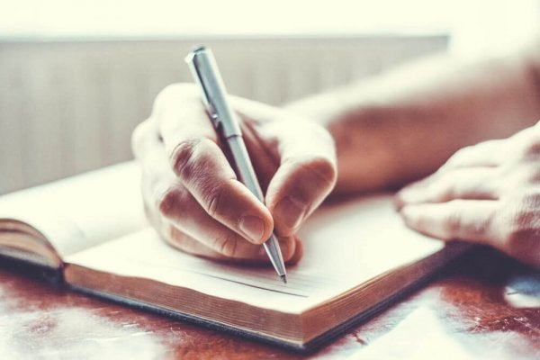 a person writing in a diary with a pen
