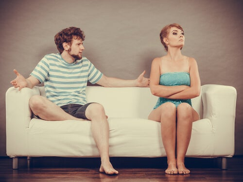 A couple having an argument on a couch.