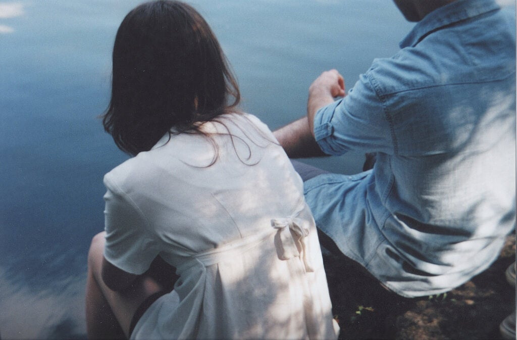 A couple sitting together near the water.