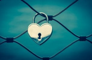 A heart shaped lock locked on a fence.