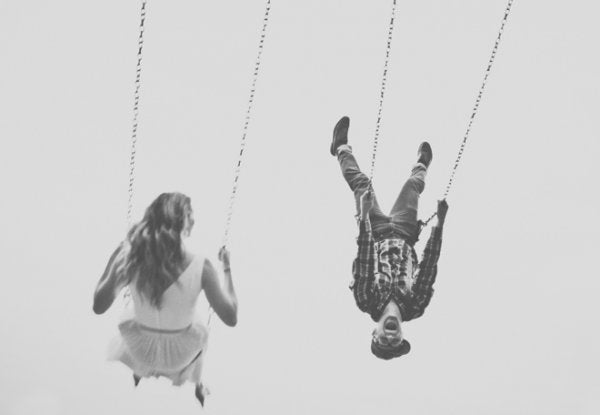 Happy people swinging on swings up high.