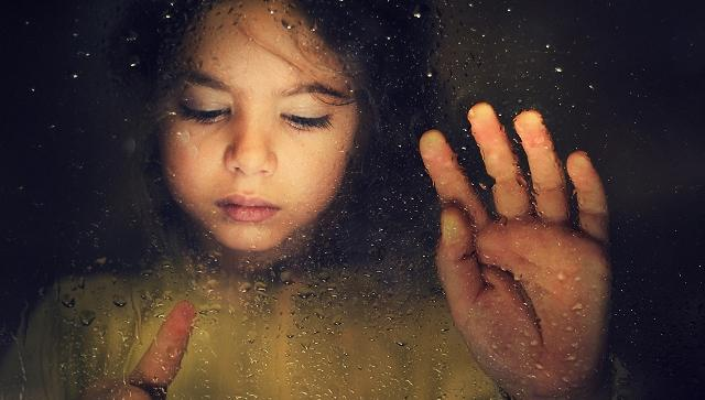 A sad little girl is drawing on a rainy window.