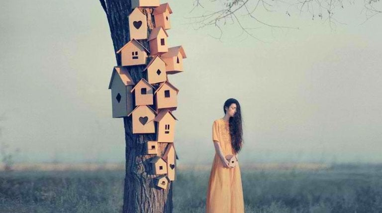 A woman next to many birdhouses.