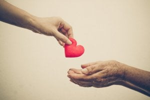 A person giving another a heart.