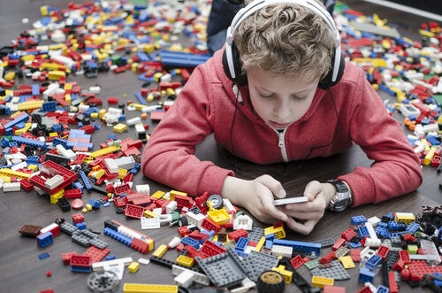 a little boy surrounded by toys but playing on a mobile device