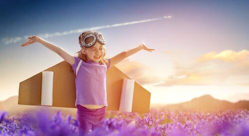 a child wearing cardboard wings like a plane