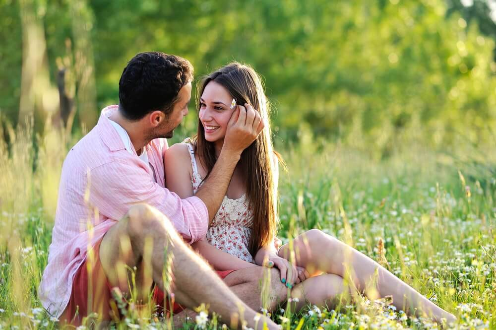 A couple in love is sitting together in the grass.