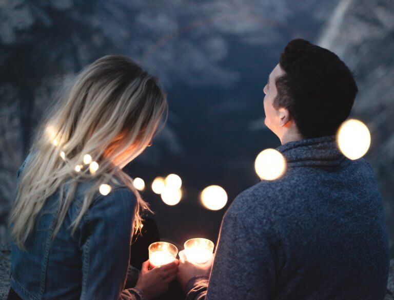 A couple is surrounded by lights and holding candles.