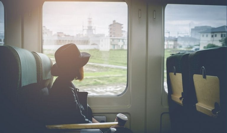 A girl is sitting on board a train.