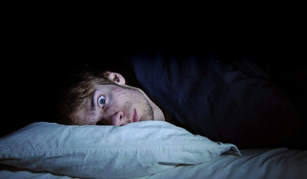 a man lying in bed with eyes wide open