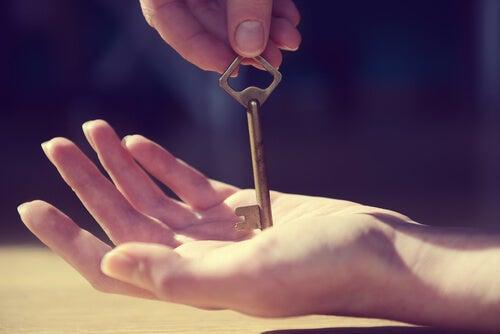 A key piercing a hand.
