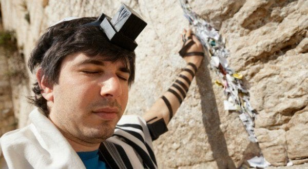 a man at the wailing wall of Jerusalem