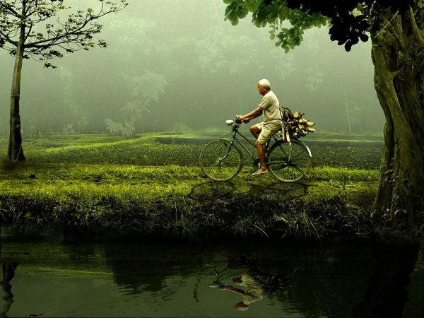 You are capable: an older man riding a bicycle by a pond.