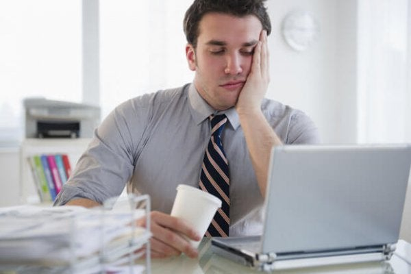 overworked, stressed office worker at his laptop with coffee