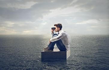 A boy looking through binoculars in an ocean.