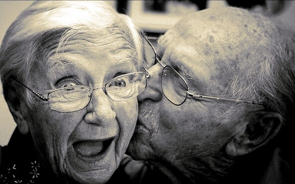 an old man kissing his wife
