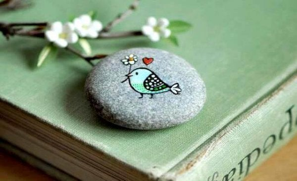 A bird carrying a flower, painted on a stone.