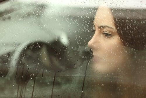 A sad woman inside a rainy car window.