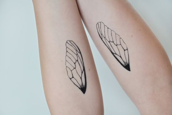 Two wings tattooed on legs.