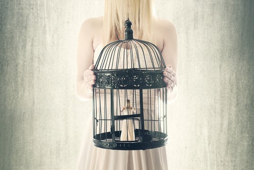 a girl holding a birdcage with herself inside