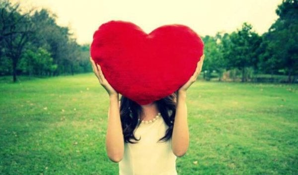A woman holding a big, red heart over her head.