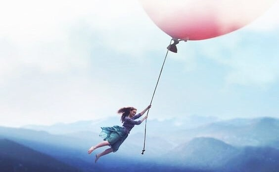 a girl holding on to a giant balloon over the mountains