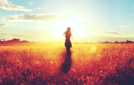 a woman standing in front of a bright sun in a field