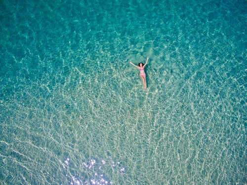 A paradise: a woman floating on a beautiful blue ocean.