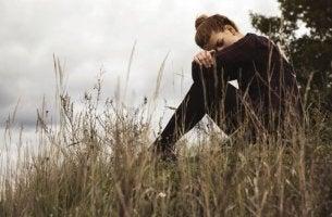 Woman is sitting in a field feeling guilt