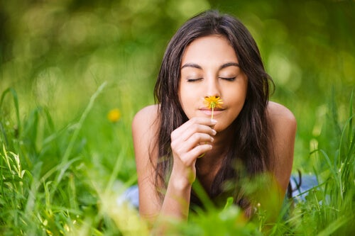 woman smelling flower thinking about living in the present