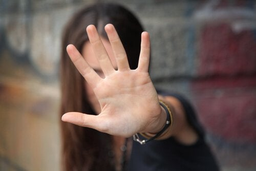 A woman holding her hand up to say STOP.