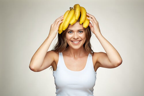 A woman holding bananas on her head.